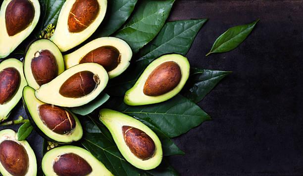 Fresh avocado with leaves on black background stock photo