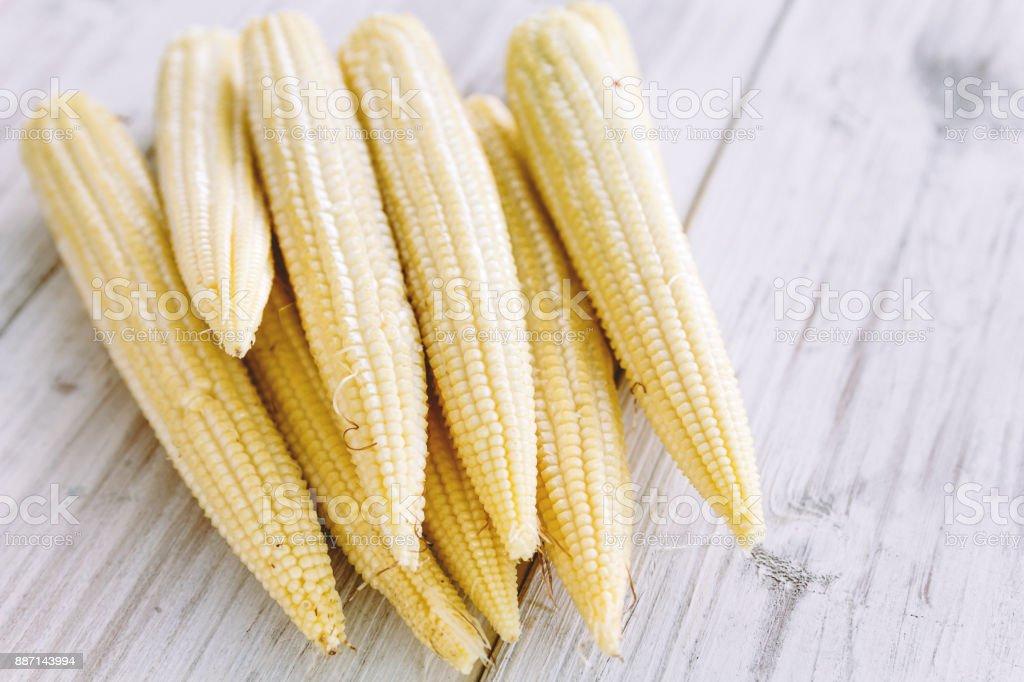Fresh Baby corn on wooden background stock photo