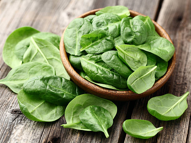 fresh baby spinach leaves in a bowl on a wooden table - spinach stock photos and pictures