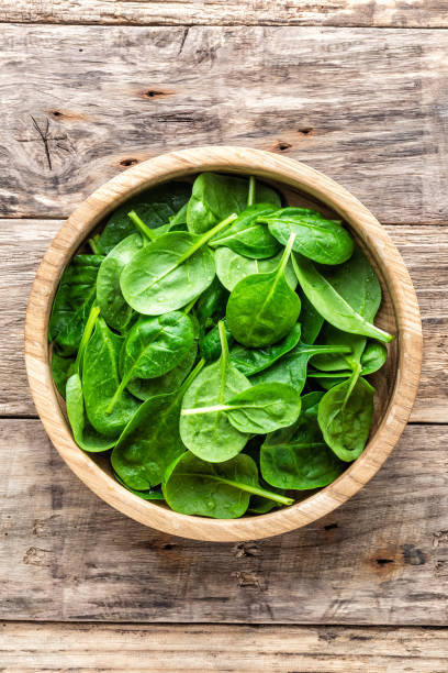Fresh baby spinach leaves in bowl on wooden background stock photo