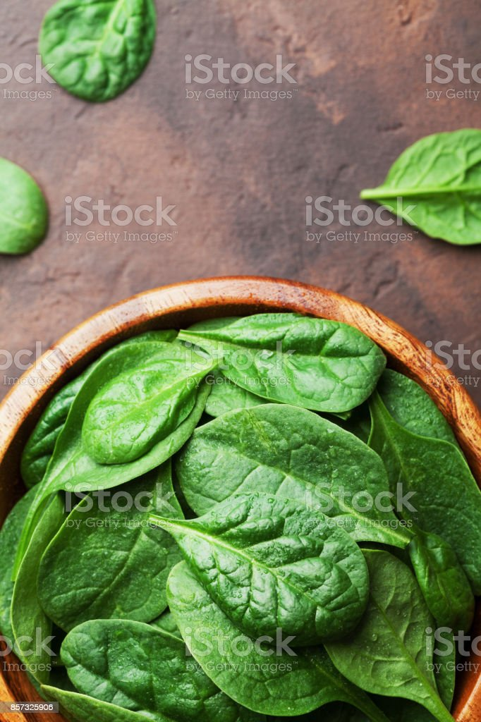 Fresh baby spinach leaves in wooden bowl on rustic stone table top view. Organic healthy food. stock photo