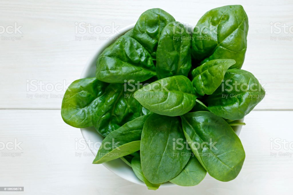 fresh baby spinach leaves on white wooden background stock photo