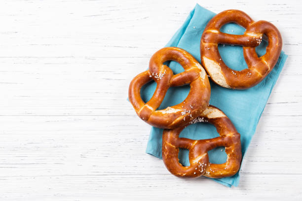 Fresh backed pretzels on a blue towel, beer snack, top view with copy space stock photo