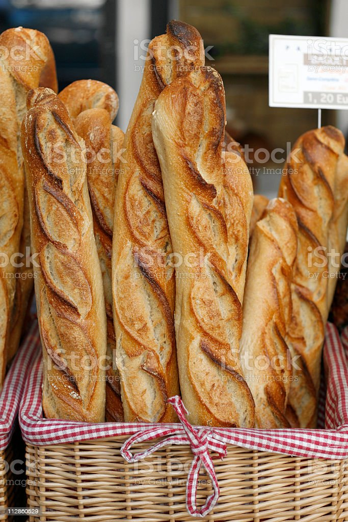 Fresh baguettes in a basket lined with red and white gingham stock photo