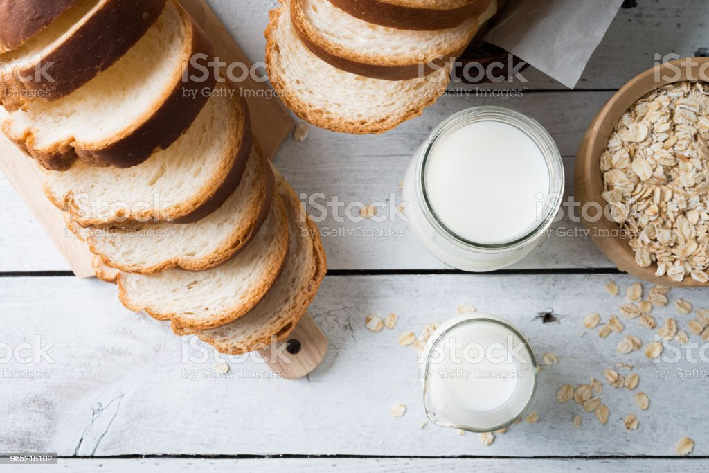 Fresh baked bread and sliced bread on rustic wooden table zbiór zdjęć royalty-free
