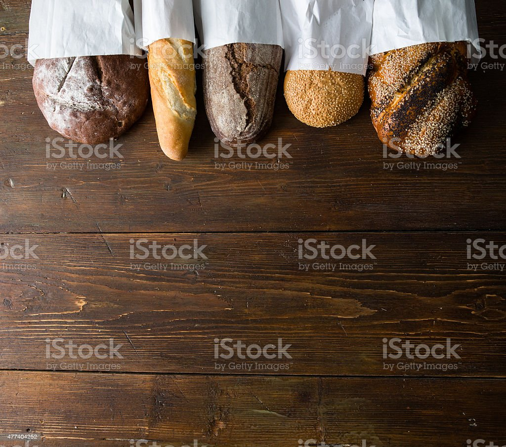 Fresh baked bread at wooden table stock photo