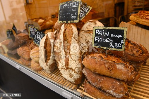This is a close up photograph of fresh baked bread on retail display in the storefront window of a bakery in Paris, France.