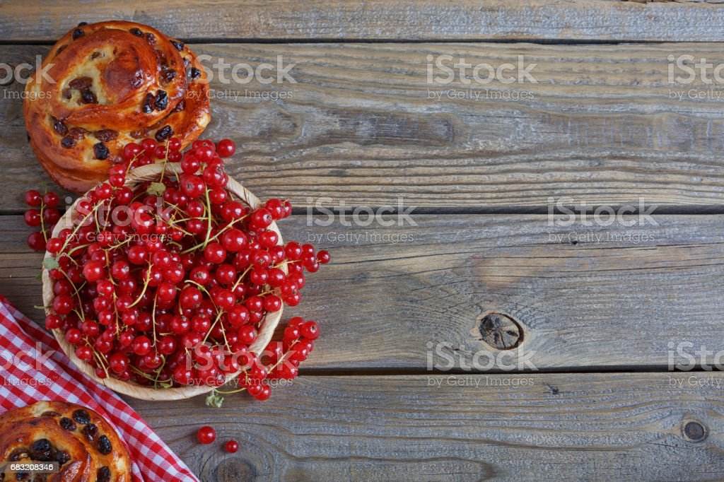 Fresh baked buns with red currant on rustic wooden table royalty-free stock photo