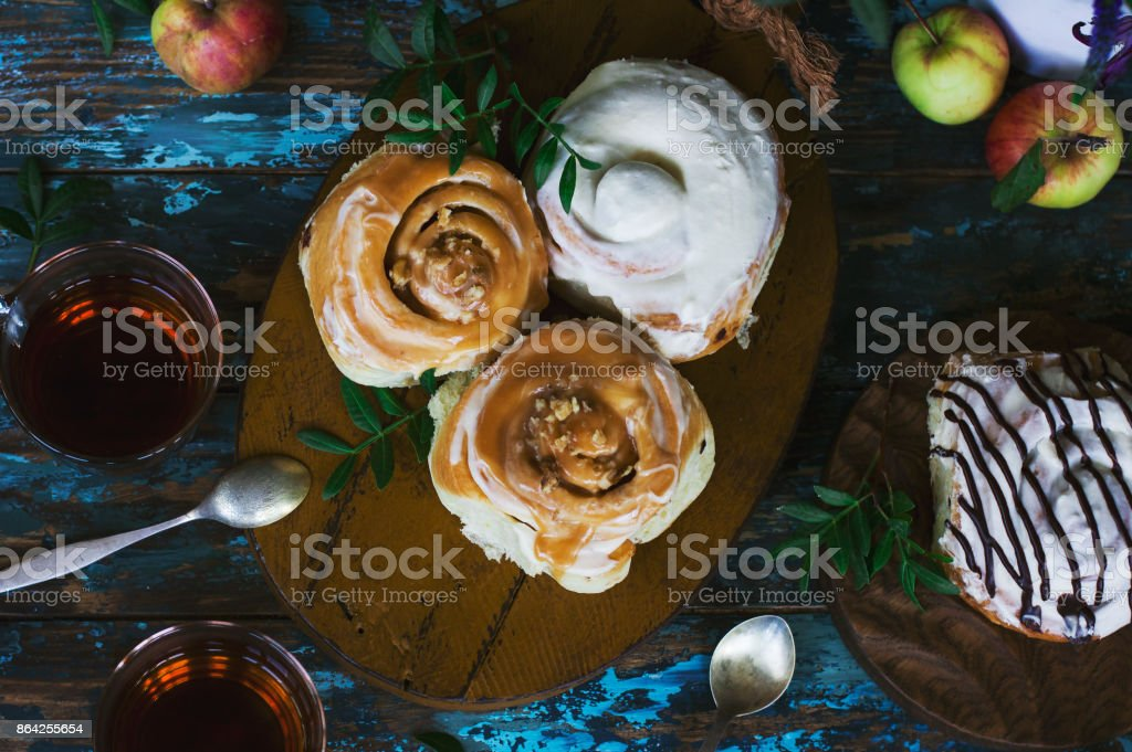 Fresh baked cinnamon rolls with frosting, apples and tea on the shabby background. View from top royalty-free stock photo