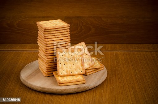 istock Fresh baked cream crackers in stacks over wooden cutting circle board on wood table and dark brown background with copy space for text decoration 812936948