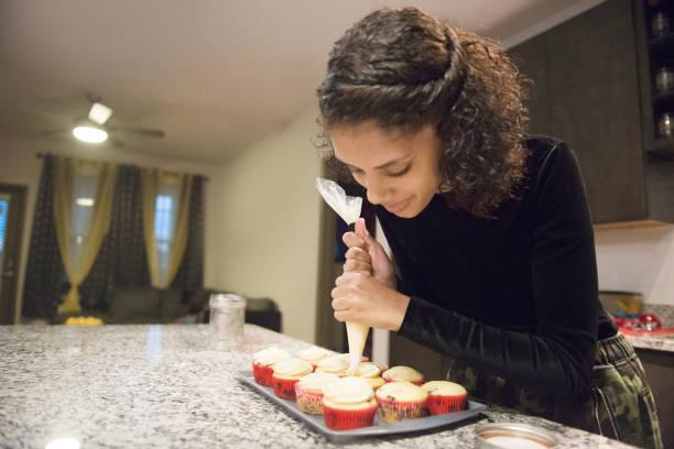 frisch gebackene hausgemachte muffins garniert mit sahnehäubchen in küche usa - cupcake, zuckerguss stock-fotos und bilder