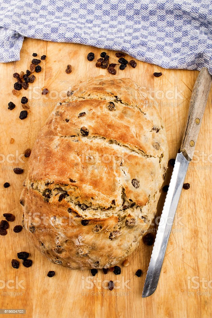 fresh baked raisin bread with knife on a wooden board stock photo