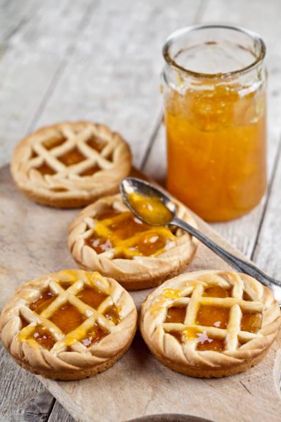 frisch gebackene torten mit marmelade-füllung und aprikosenmarmelade in glasgefäß auf schneidebrett auf rustikalem holztisch. - crostata stock-fotos und bilder