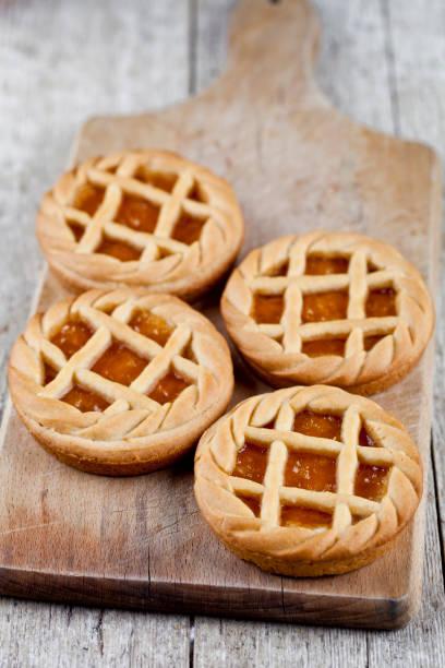 frisch gebackene torten mit marmelade oder aprikosenmarmelade füllen auf schneidebrett auf rustikalem holztisch - crostata stock-fotos und bilder