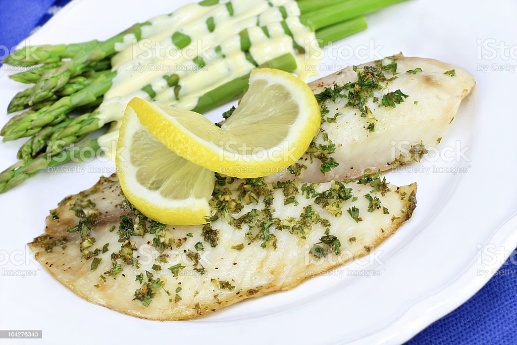 Fresh baked Tilapia fish dinner with asparagus and Hollandaise stock photo