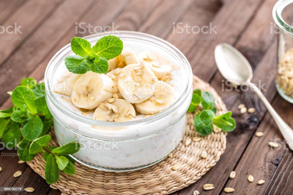 Fresh banana yogurt with oats, delicious dessert for healthy breakfast stock photo