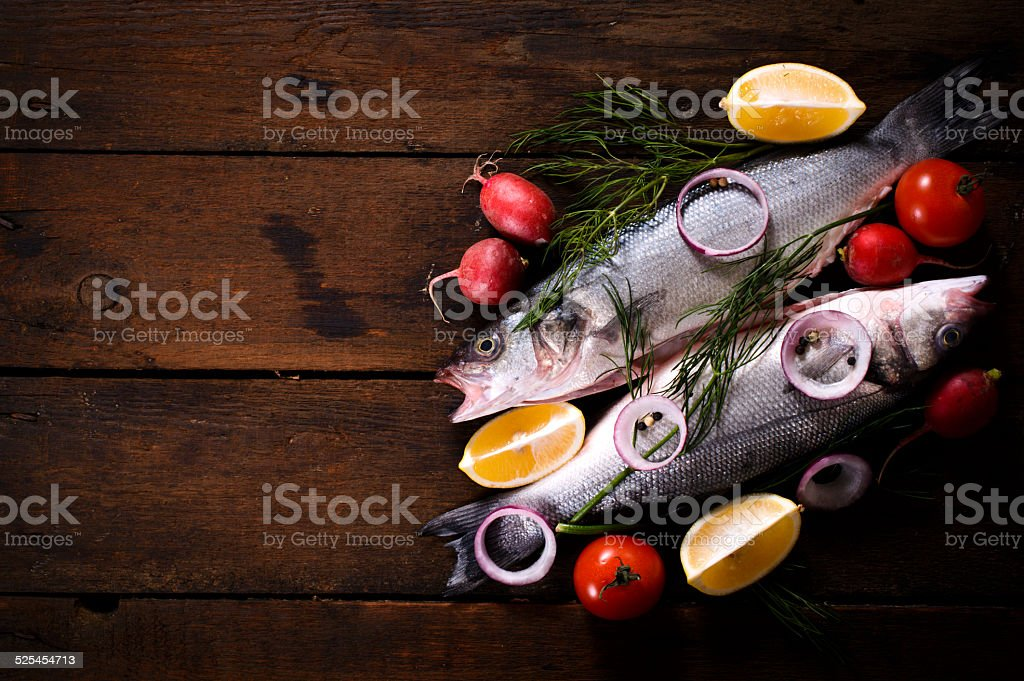Fresh bass fish on wooden background stock photo