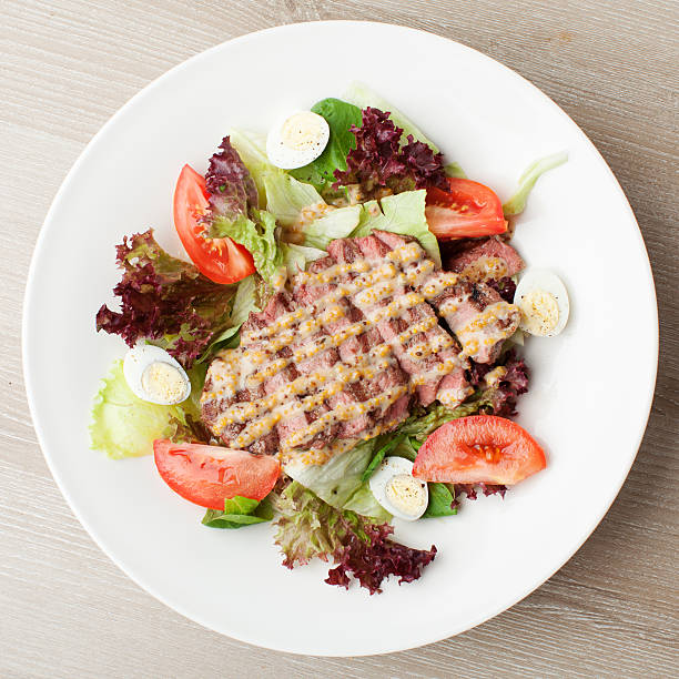 Fresh beef salad with lettuce, tomatoes, boiled eggs, sauce stock photo