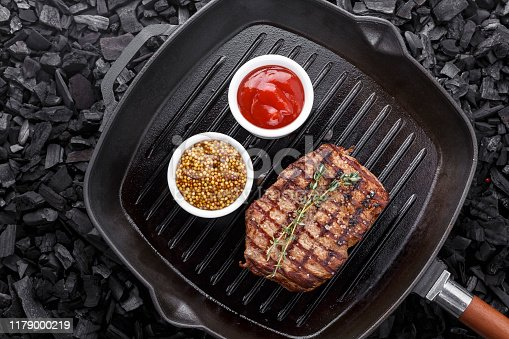 808351106 istock photo fresh beef steak with spices in a grill pan. 1179000219