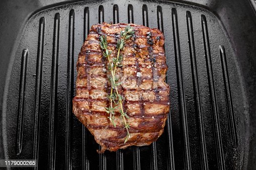 808351106 istock photo fresh beef steak with spices in a grill pan. 1179000265