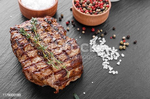 808351106 istock photo fresh beef steak with spices on a black background. 1179000183