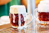 Fresh beer with foam from tap in a german traditional mug