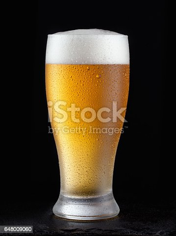 istock Fresh beer in glass on a black background. 648009060