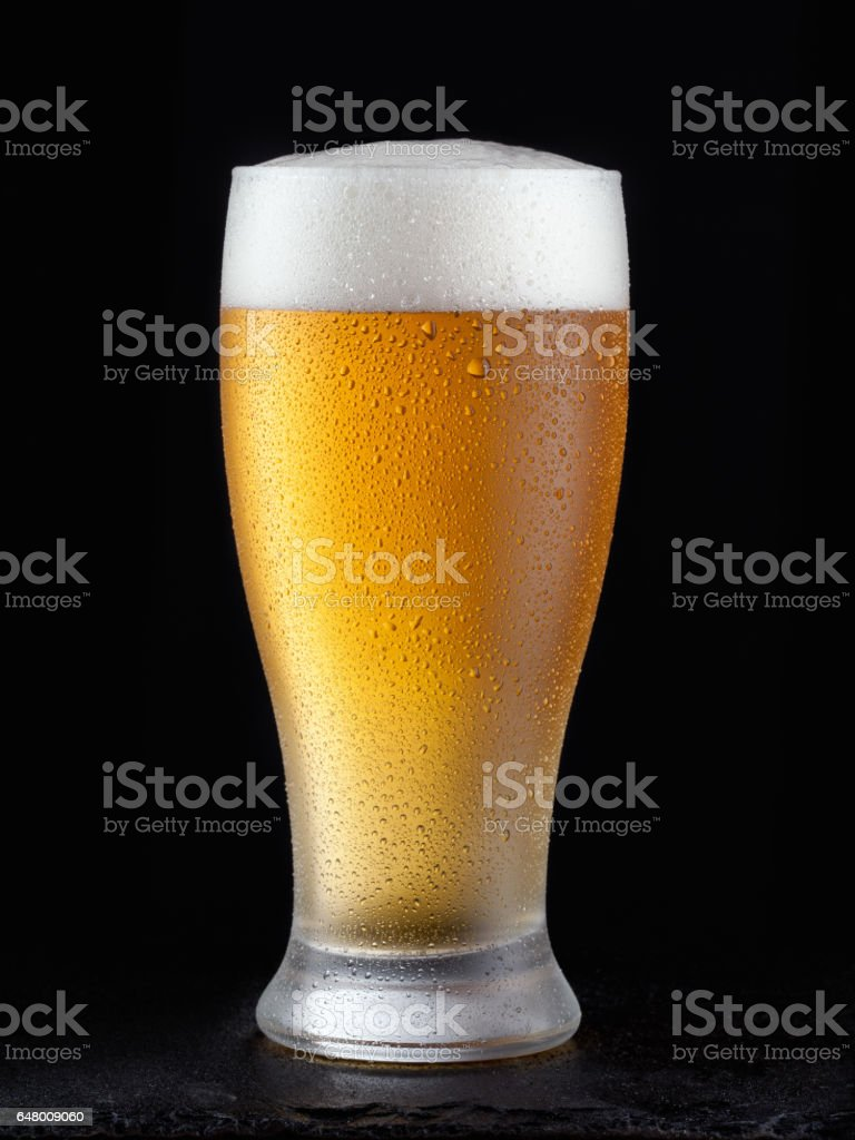 Fresh beer in glass on a black background. stock photo