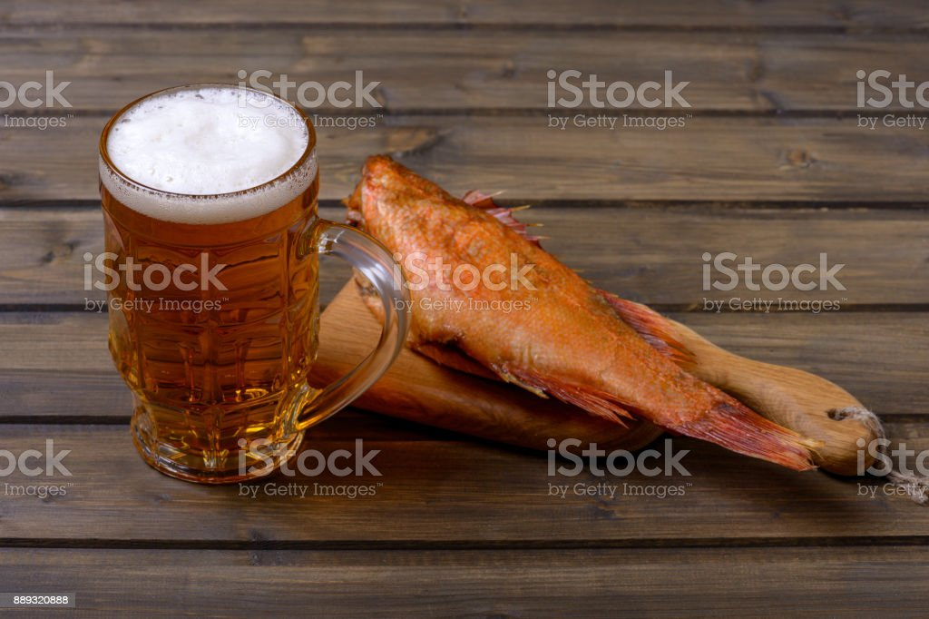 Fresh beer in mug with foam and smoked fish on table stock photo