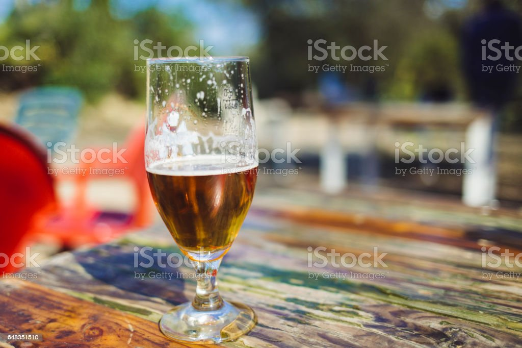 Fresh beer isolated on a wooden table stock photo