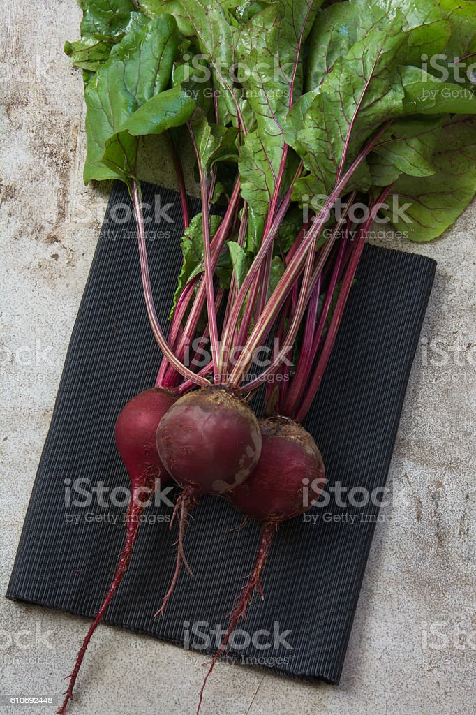 Fresh beet on black napkins on rustic table. Top view. stock photo