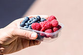 the guy is holding a tray of raspberries and blueberries. Vitamin-rich fruits are packaged in boxes. box on light background with copy space.