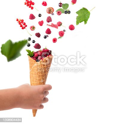 879258868 istock photo Fresh berries falling into waffle cornet  in child's hand isolated on white with copy space 1208904434
