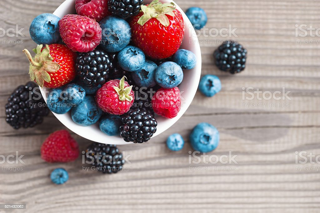 Fresh berries in a basket on rustic wooden background. stock photo