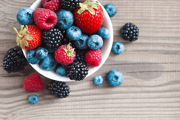 fresh berries in a basket on rustic wooden background. - berry stock photos and pictures