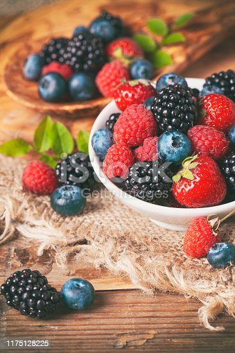 Fresh berries in a bowl on rustic wooden background