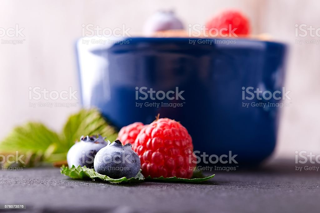 Fresh berries in front of creamy dessert in blue bowl stock photo