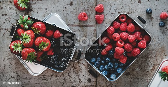 517278430 istock photo Fresh berries in metal lunchboxes over grey background, top view 1218718333