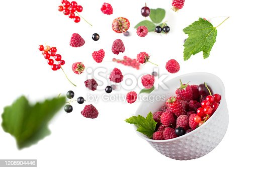 879258868 istock photo Fresh berries mix with green leaves flying and falling down into a bowl on white background 1208904446