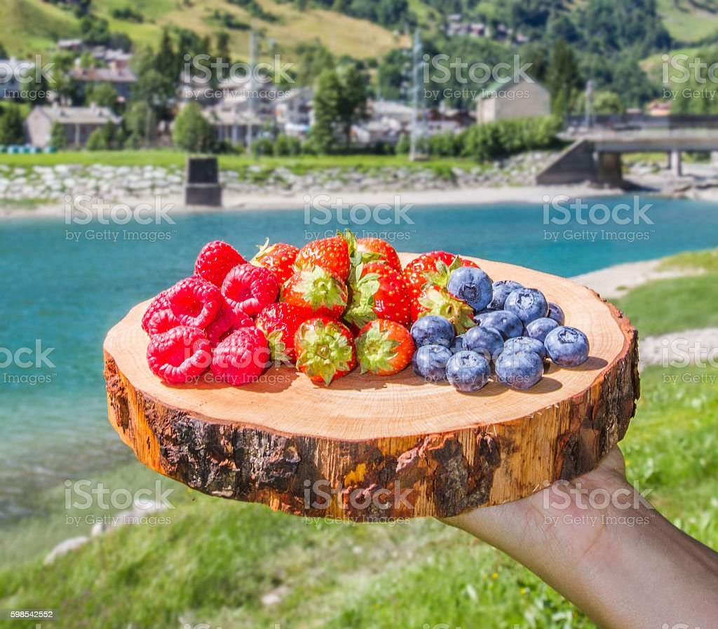 fresh berries on wooden cutting board with background mountains photo libre de droits