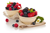 """""""Close-up shot of fresh berries in bowls, isolated on white."""""""