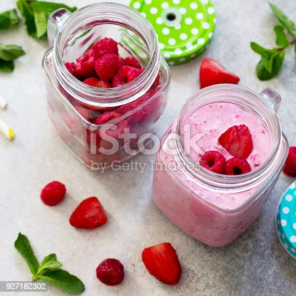 istock Fresh berry smoothies and fresh strawberries and raspberries on a gray stone or slate background. The concept of proper nutrition and health or detoxification. Copy space. 927162302