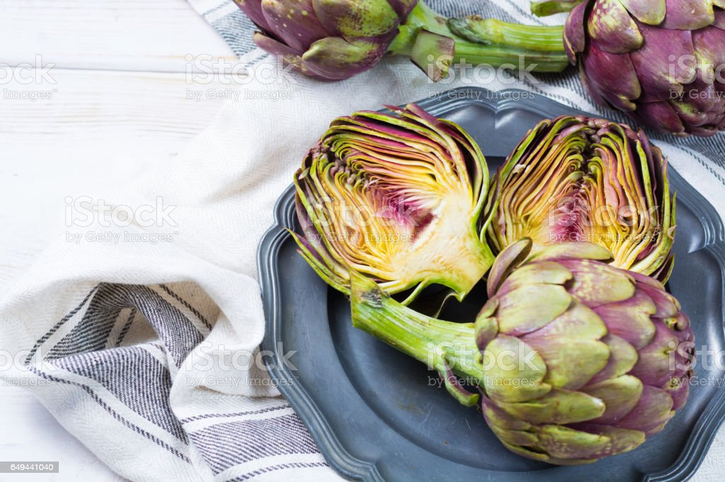 Fresh big Romanesco artichokes green-purple flower heads ready to cook - foto stock