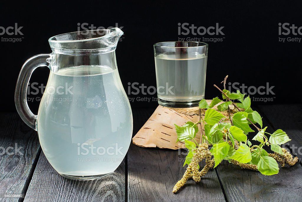 Fresh birch juice in a glass and birch branches foto