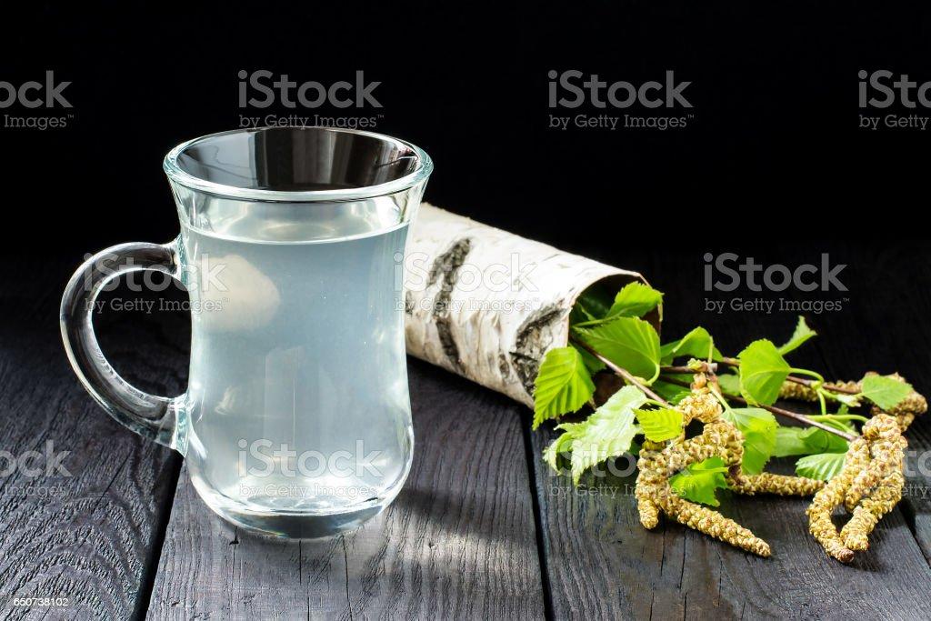 Fresh birch sap in een glas en berken takken foto