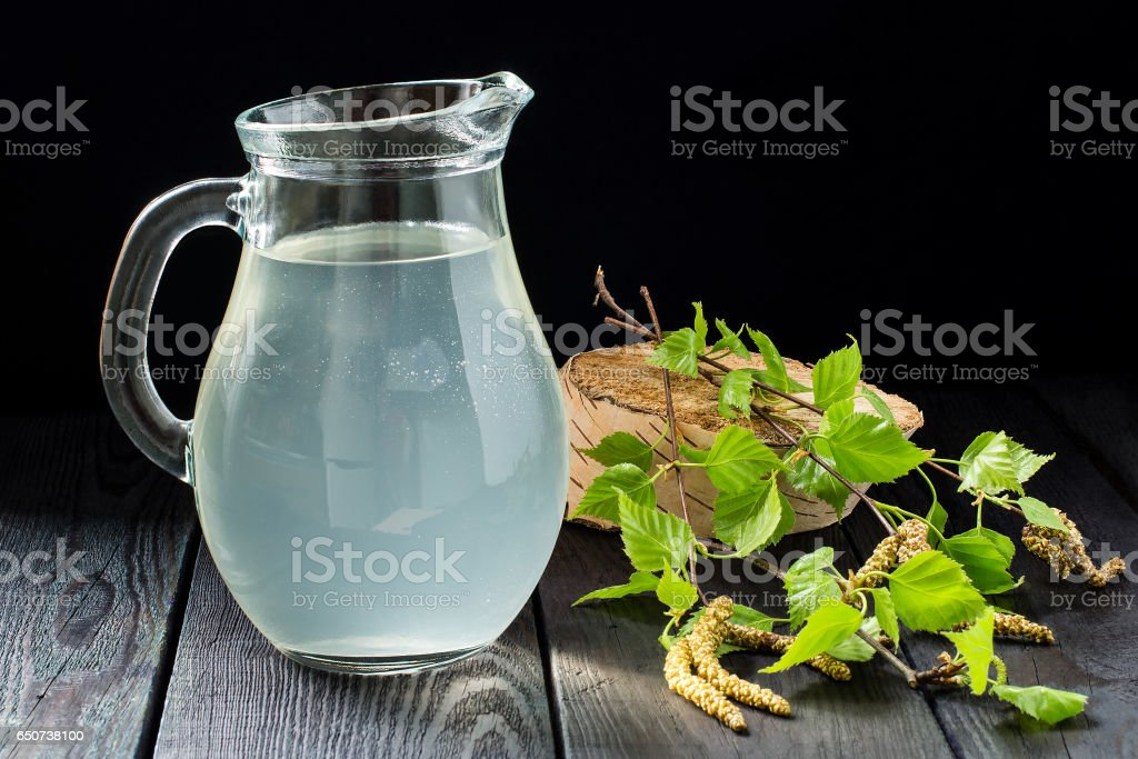Fresh birch sap in een kruik en berken takken foto