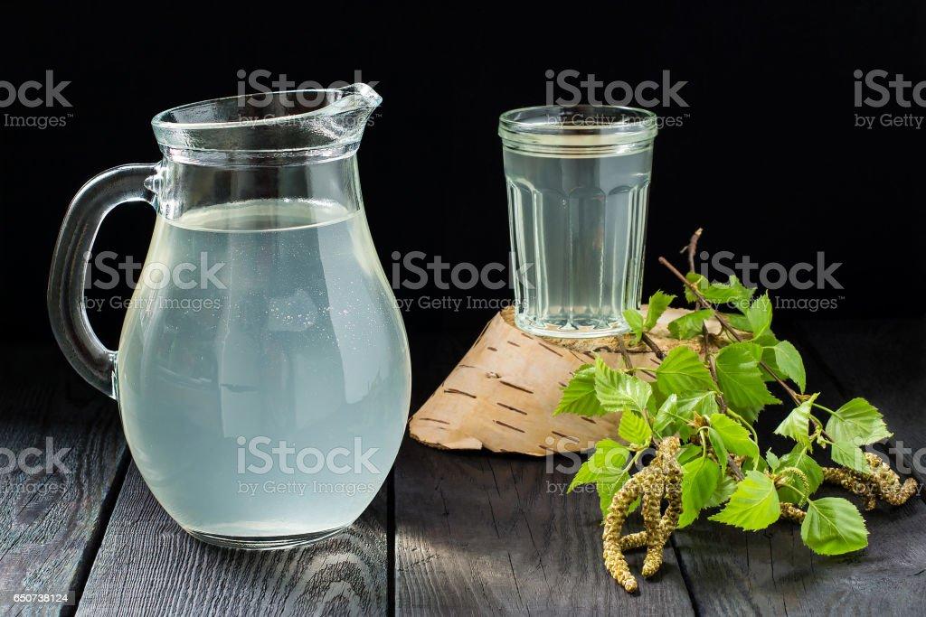 Fresh birch sap in een kruik en glas en berken takken foto