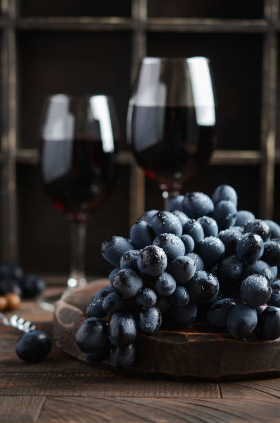 Fresh Black Grapes and Red Wine on Wooden Table Fresh Black Grapes and Red Wine on Wooden Table Selective Focus merlot grape stock pictures, royalty-free photos & images
