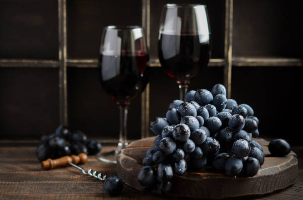 Fresh Black Grapes and Red Wine on Wooden Table stock photo