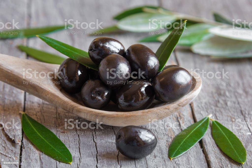 Verse zwarte olijven op een houten lepel foto